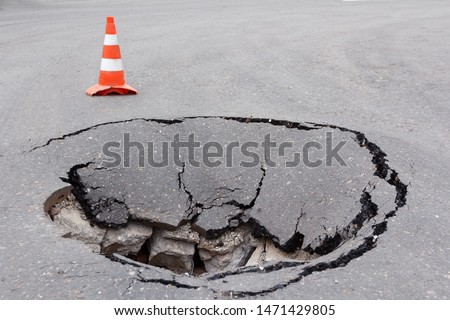 Deep sinkhole on a street city and orange traffic cone. Dangerous hole in the asphalt highway. Road with cracks. Bad construction. Damaged asphalt road collapse and fallen.