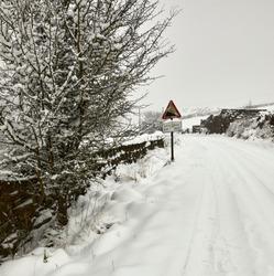 Deep snow after daylong snowfall on moorland single track lane in Nidderdale.