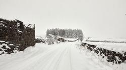 Deep snow after daylong snowfall on moorland single track lane in Nidderdale