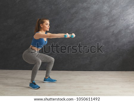 Deep squat. Side view of young beautiful woman in sportswear doing squat exercises, holding dumbbells at gym, copy space