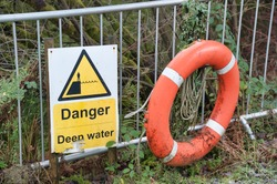 Deep water danger yellow symbol sign and red lifebuoy