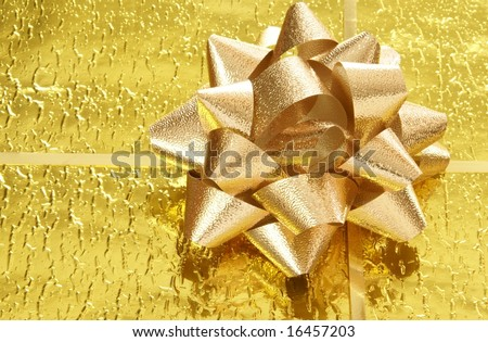 Deep yellow gold bow and ribbon on textured gold foil