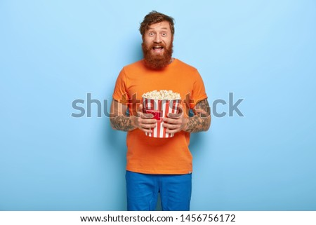 Deeply entertained ginger man watches comedy, enjoys spare time, holds bucket with popcorn, dressed casually, spends evening in cozy domestic atmosphere. Young guy watches film, eats junk food
