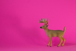 Deer toy isolated over fuchsia background. Plastic animals toys.