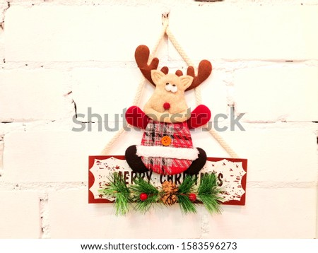 Deer, toys, inscription and Christmas holiday decorations. The decorations are attached to the wall in white and serve as decoration in the interior of the house.