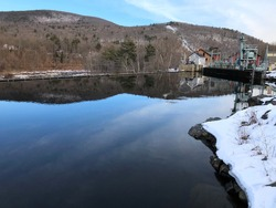 Deerfield River Dam and Infrastructure With Water, Snow-Covered Ground, and Winter Hills and Blue Sky Seen From Buckland Side of Shelburne Falls, Massachusetts