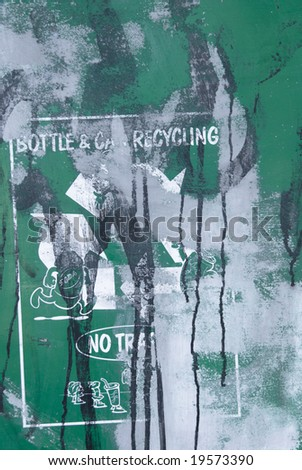 Defaced recycling sign seen in a run-down park