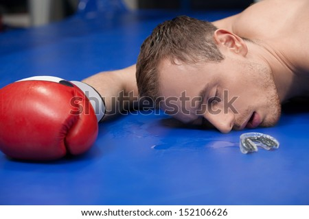 Defeated boxer. Close-up of defeated boxer lying down on the boxing ring with closed eyes