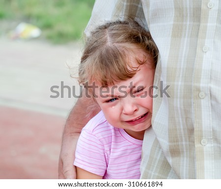 defenseless little girl crying under the protection of the parent