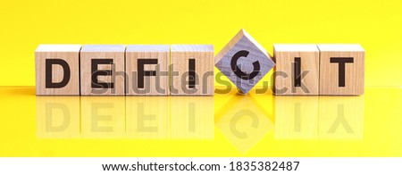 deficit word written on wood block. deficit word is made of wooden building blocks lying on the yellow table. sales, business concept, yellow background Foto stock ©