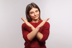 Definitely no, prohibited access! Portrait of girl in shaggy sweater crossing hands, showing x sign, stop gesture, warning of end finish, forbidden way. indoor studio shot isolated on gray background