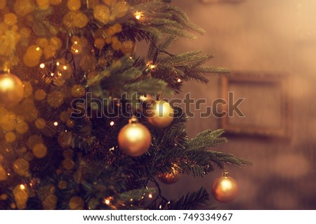 Defocus beautiful dark background. decorations on a Christmas tree and glare of lights #749334967