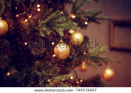 Defocus beautiful dark background. decorations on a Christmas tree and glare of lights - Shutterstock ID 749576407