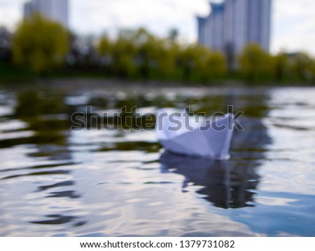 Defocus white paper boat in blue water. Symbolizes uncertainty and unpredictability of the future. You never know what to expect in life. Concept of blurry perspective. #1379731082