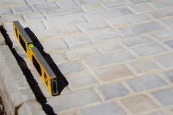 Defocus yellow spirit level on paving stone footpath. Monotone light gray brick stone pavement on the ground. Texture background. Pattern. Construction industry. Out of focus.
