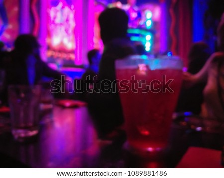 Defocused abstract blurred scene of people enjoy drinking and eating in a dark night club #1089881486