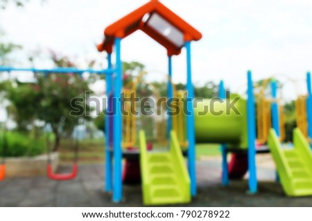 Defocused and blurred image of colorful playground in public park, slide and swing on yard activities for children. Exercise and healthy care concept.