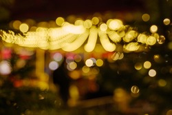 Defocused and night vibrance atmosphere of Weihnachtsmarkt, annual Christmas market, with circle Bokeh from decorated light bulbs.