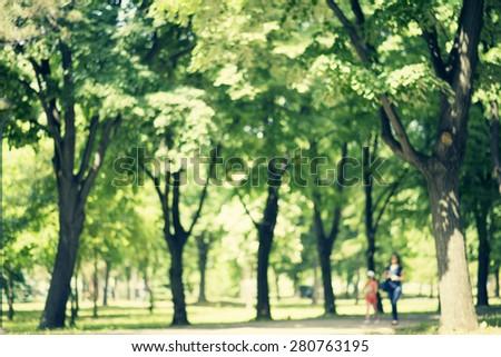 Defocused background of park in spring or summer season, blurred people walking, retro colors