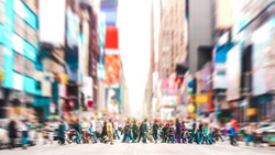 Defocused background of people walking on zebra crossing on 7th avenue in Manhattan - Crowded streets of New York City during rush hour in urban area - Vivid sunset filter with soft sharp focus