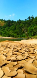 defocused background of tropical natural scenery on the river bank with dry moss and hilly forest