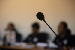Defocused black microphone in conference presentation room with defocused people setting in the background