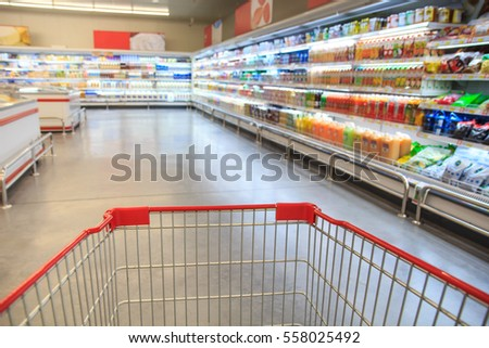 Defocused blur of supermarket cart with dairy products. Blur background with bokeh. Defocused image #558025492