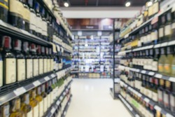 defocused/ Blurred image of bottles of wine on the shelves in supermarket.