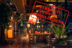 Defocused, blurred view of interior of an upmarket bar or restaurant, empty and closed due to covid 19 with Polish notice Closed due to Coronavirus