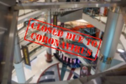 Defocused, blurred view of interior of an upmarket shopping centre or mall, empty and closed due to coronavirus or covid 19 pandemics