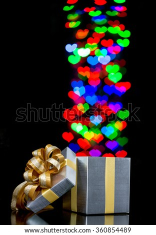 Defocused bokeh lights heart shaped are moving out of open gift box
