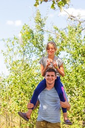 Defocused brother giving sister ride on back. Portrait of happy girl on man shoulders, piggyback. Family playing outside. Summer holidays smiling people concept. Funny horns. Out of focus.
