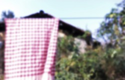 Defocused bukeh background of a cloth hanging under the sky.