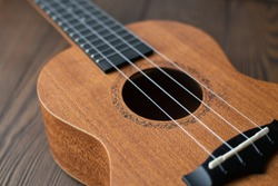 Defocused close up ukulele strings, body, soundhole, bridge and neck on brown wooden background. Folk music instruments. Country style.