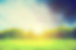 Defocused image, blur of fresh green spring summer landscape with sun shining.