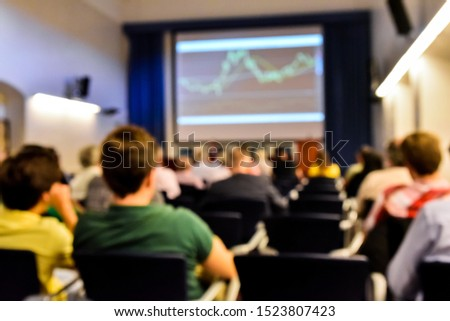 Defocused image of an economics seminar with stock market graphs, with unrecognizable people. #1523807423