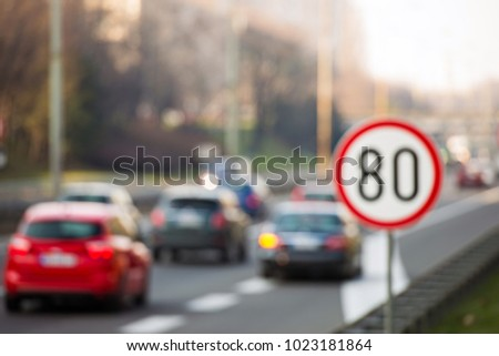 Defocused image of speed limit sign showing 80 km/h speed limit with a traffic in the background #1023181864