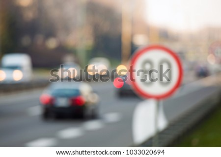 Defocused image of speed limit sign with a traffic in the background on a highway #1033020694