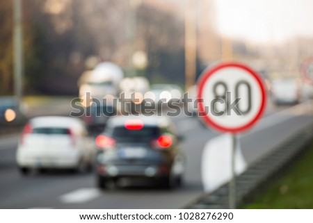 Defocused image of traffic sign showing 80 km/h speed limit on a highway full of cars #1028276290