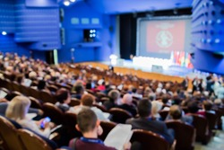 Defocused image. People in the auditorium. International conference. Flags of different countries on stage.