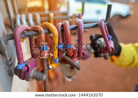 Defocused of male hand rigger inspector wearing black glove conducting safety inspecting colorful of pinky lifting lug prior to used on opening field construction site