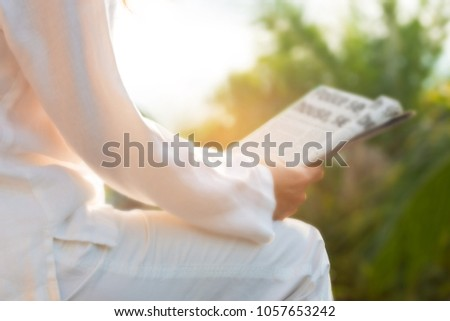 Defocused of woman reading newspaper in backyard early morning ,old fashioned media concept.