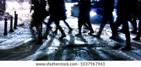 Defocused people silhouettes crossing the street in snowy winter night , with driving cars aproaching  #1037967961