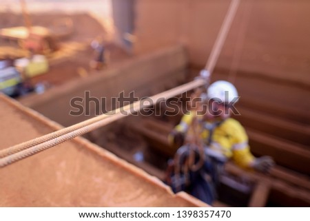 Defocused rope access abseiler wearing safety full protection helmet harness working at height on tension line anchor point connecting with pulley descending construction site Perth, WA