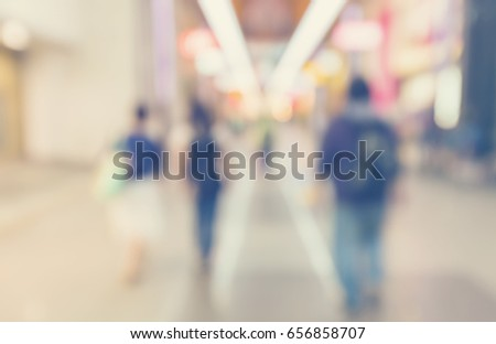Defocused shopping mall interior with groups of people walking in pastel colors #656858707