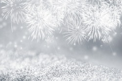 Defocused silver and gray fireworks and bokeh on gliter paper at New Year and copy space. Abstract background holiday.