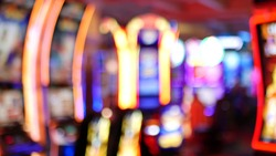 Defocused slot machines glow in casino on fabulous Las Vegas Strip, USA. Blurred gambling jackpot slots in hotel near Fremont street. Illuminated neon fruit machine for risk money playing and betting.