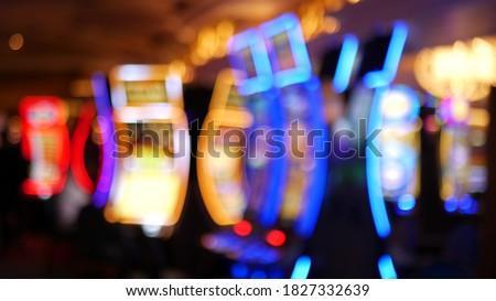 Defocused slot machines glow in casino on fabulous Las Vegas Strip, USA. Blurred gambling jackpot slots in hotel near Fremont street. Illuminated neon fruit machine for risk money playing and betting. Stockfoto ©