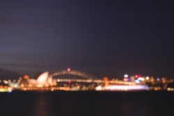 defocused Sydney harbour bridge and operahouse, light night bokeh idea for background.