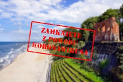 Defocused view of beach, sea and ruins of church in Trzesacz, Poland. Empty and closed due to covid 19 with Polish notice Closed due to Coronavirus